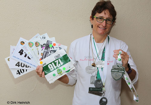 Monika Großmann, the only rider who has participated in all 15 Desert Dash mountain bike races and completed all of them. Here she is with most of her bib numbers and medals. In her left hand is the medal which she treasures most: the medal for her first solo ride in December 2019.
